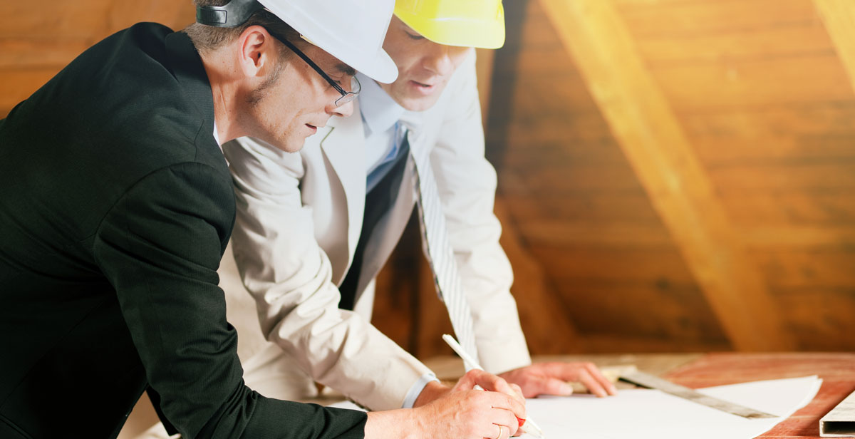 two guys in hard hats looking at house blue print inside attic