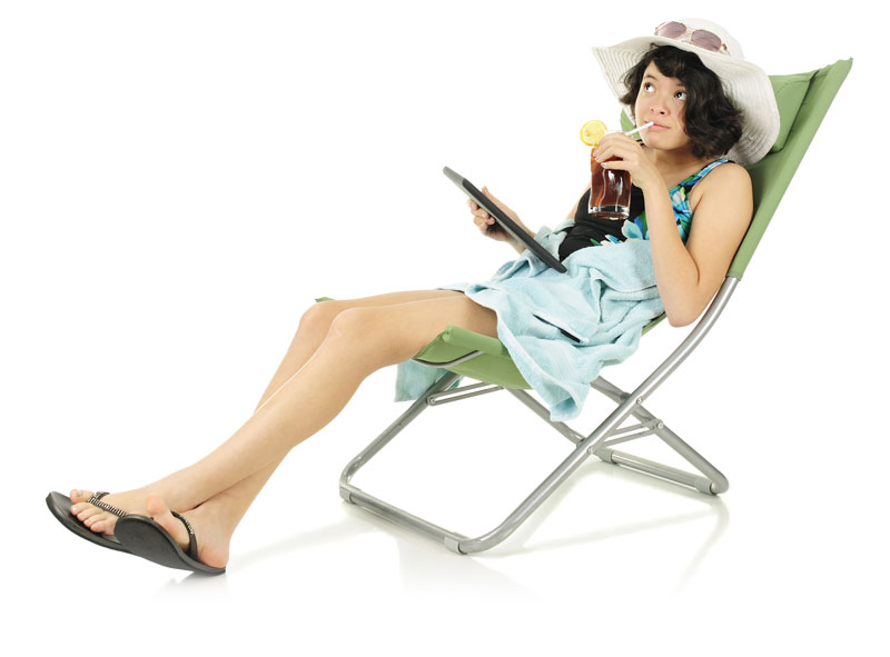 girl sitting beach lawn pool side chair sipping on tea with ipad