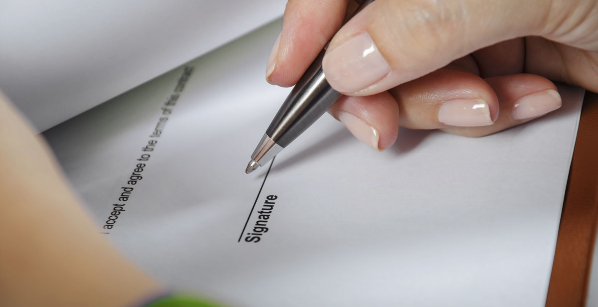 woman hand signing a contract or document with black pen list of must haves for property modifications