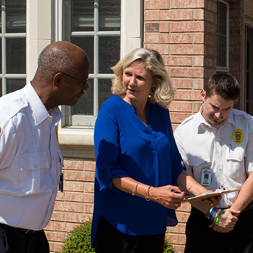 facility maintenace photo of woman in blue shirt with two men in uniform looking at clipboard outside of community center