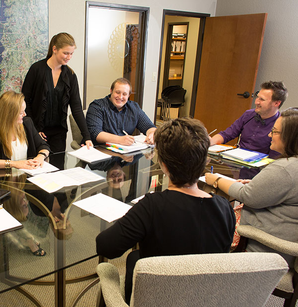 Neighborhood Management team at conference table happy smiling and planning
